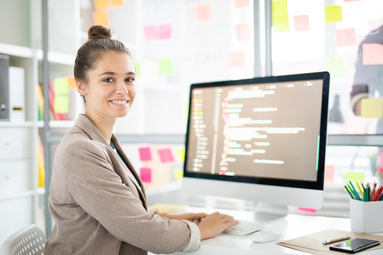 Young casual woman sitting by desk in front of camera and analyzing coded data on computer screen