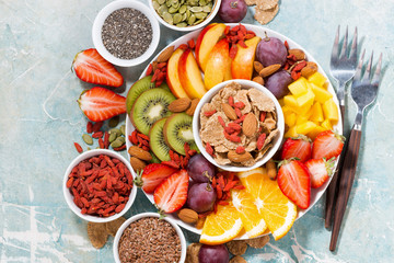 plate of fresh seasonal fruits and superfoods on rustic background, top view