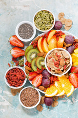 plate of fresh seasonal fruits and superfoods on rustic background, vertical, top view