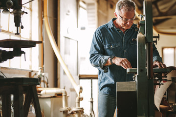 Mature male carpenter working on band saw
