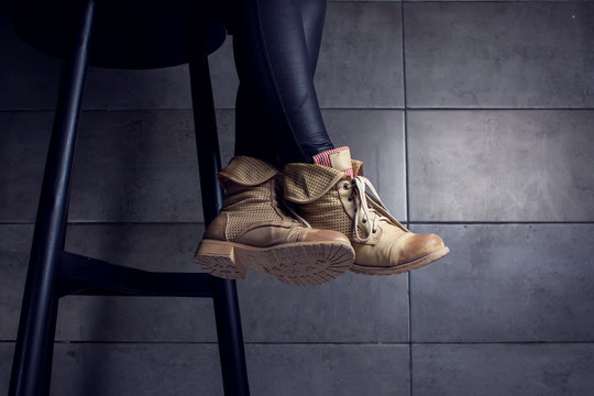 Low section of woman wearing boots sitting at bar counter in cafe
