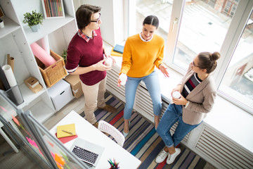 Young casual colleagues standing by office window and discussing organization moments during coffee break