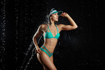 Young beautiful girl with a slim athletic body dressed in a mint green bikini posing on a black background in spray of water