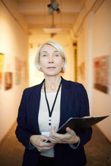 Waist up portrait of mature female manager holding clipboard posing in art gallery looking at camera
