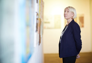 Side view portrait of pensive mature woman looking at paintings in art gallery, copy space
