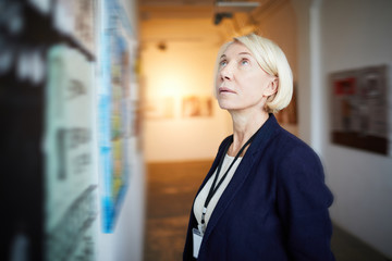 Portrait of pensive mature woman looking at paintings in art gallery, copy space