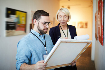 Waist up portrait of modern bearded man buying picture in art gallery or museum, copy space