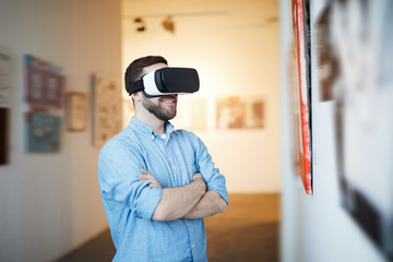 Waist up portrait of contemporary man wearing VR headset in art gallery, copy space