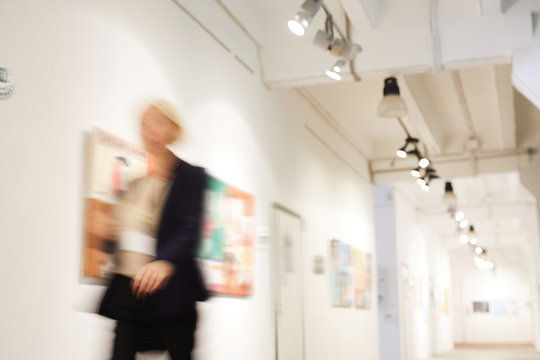 Blurred shape of unrecognizable woman walking in art gallery hall, copy space