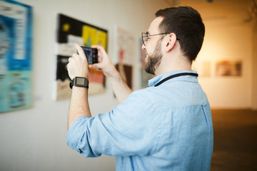 Side view  portrait of smiling  man taking smartphone photo of painting in art gallery, copy space