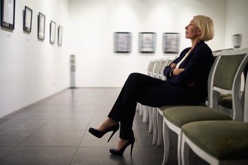 Side view full length portrait of elegant woman sitting on velvet chair looking at pictures in art gallery or museum, copy space