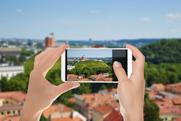 A man is making a photo of Vilnius panorama with a view of the castle mountain in a summer sunny day on a mobile phone
