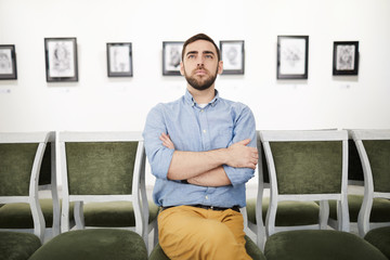 Portrait of pensive bearded young man looking at pictures in art gallery or museum while sitting on velvet chair, copy space