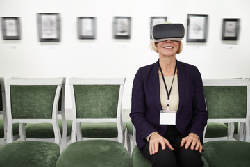Portrait of smiling mature woman wearing VR while looking at pictures in museum or art gallery, copy space