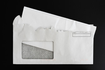top view of folded letter in torn open envelope on black background