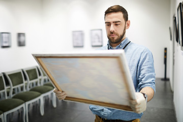 Waist up portrait of modern bearded man buying picture in art gallery, copy space