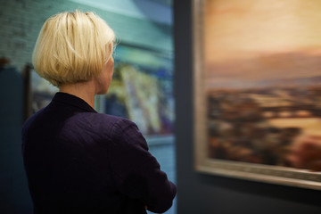 Back view portrait of unrecognizable woman looking at pictures in modern art gallery or museum,...