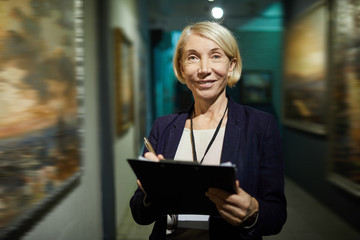 Waist up portrait of smiling mature woman holding clipboard while looking at camera in art gallery or museum, copy space