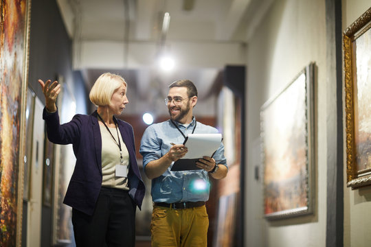 Portrait of two cheerful museum workers discussing paintings walking in art gallery, copy space