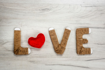Word love with plush heart shape on wooden background