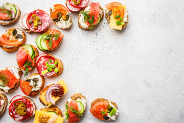 Assorted spanish tapas with fish, sausage, cheese and vegetables. White background, top view.