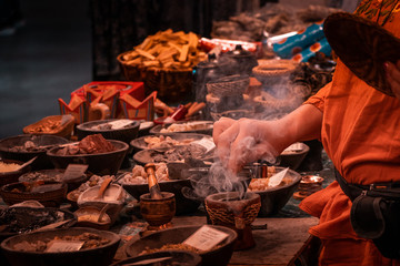 Shaolin Monk life, preparing herbal medicines. Habitat and ritual tools in detail. Religion and philosophy concept. Meditation and Oriental culture in vibrant colors.