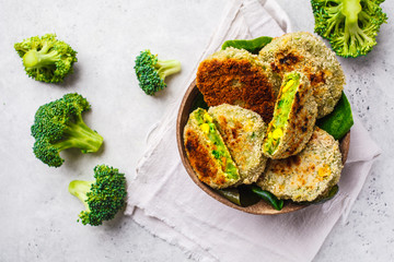 Green broccoli cutlets in coconut shell dish on white background. Wall mural