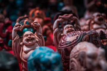 Details of the famous laughing Buddha, porcelain statue close up, macro shot, bokeh blurred background. Vivid colors and shiny textures. Indian religion concept, life path to meditation.
