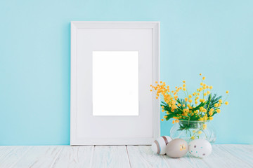 Empty white wooden frame and yellow mimosa flowers on blue background with copy space. Mockup.