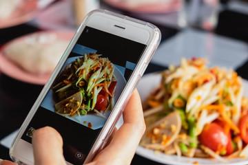Woman taking a photo of thai green papaya salad with smartphone