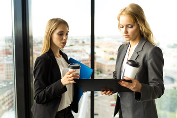 Business women discuss documents