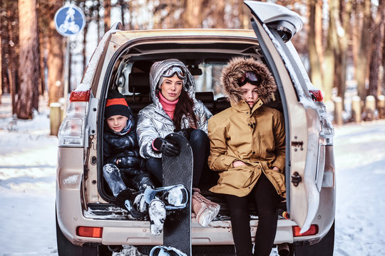 Happy family on vacation during the winter holidays. A beautiful woman and her sons dressed in warm clothes sitting on the trunk of a car