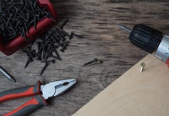 Fototapeta Narzędzia i wkręty na starym drewnianym stole obraz