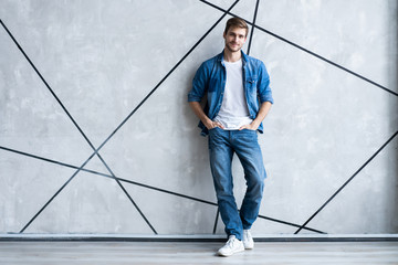 Modern and casual. Full length of handsome young man in jeans shirt looking at camera with smile while standing. Wall mural