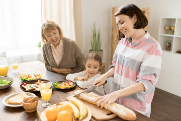 Young cheerful woman cutting bread on wooden board while preparing dinner or breakfast for family