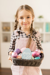 Happy little adorable girl with small basket of painted Easter eggs standing in front of camera