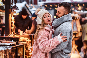 An attractive couple in love, a handsome man and charming girl cuddling and enjoying spending time together while standing at the winter fair at a Christmas time