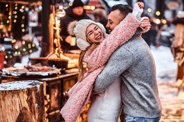 A cheerful attractive couple in love, enjoying spending time together while embracing at the winter fair at a Christmas time