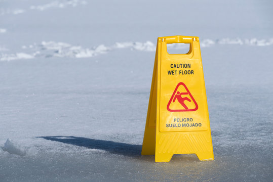 One yellow sign board caution wet floor over a frozen lake. Selective focus