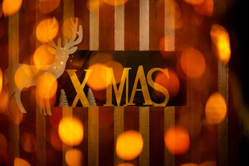 Christmas decoration: The word xmas covered with gold with white reindeer and fir trees covered by spots of light