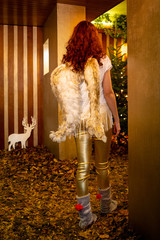 Abstract Christmas portrait of beautiful red haired young woman with angel's wings. Angel with long curly hair entering a golden room with x-mas tree and leaves on the floor