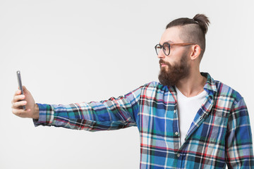 Hipster, people concept - Young hipster with beard in glasses taking selfie