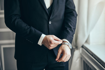 Businessman wears a jacket,male hands closeup,groom getting ready in the morning before wedding ceremony. Men Fashion