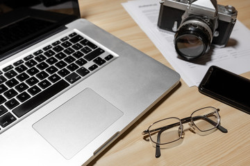 Wooden photographer desk table with camera, laptop, smartphone and eyeglasses  - Image