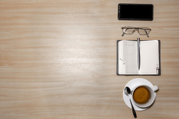 Desk with eyeglasses, notepad, smartphone, pen and a cup of tea on a wooden table. Top view with copy space. Flat lay - image