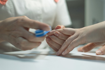 Manicurist polishes fingernails with manicure buff. Nail preparation for nail polish.