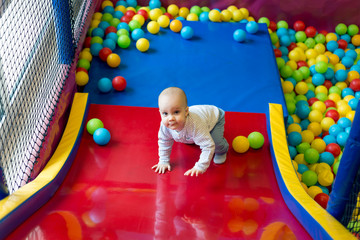 Toddler having fun in ball pit in kids amusement park and indoor play center. Child playing with colorful balls in playground ball pool. Activity toys for little kids