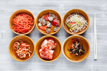 top view of various side dishes with chopsticks