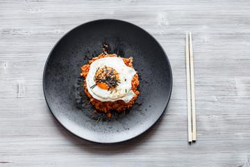 Kimchi bokkeum bap on black plate and chopsticks