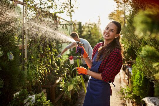 Smiling girl gardener sprays water plants in the beautiful nursery-garden on a sunny day. Working in the garden